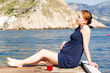 pretty pregnant woman resting near the sea