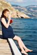 pretty pregnant woman resting near the sea