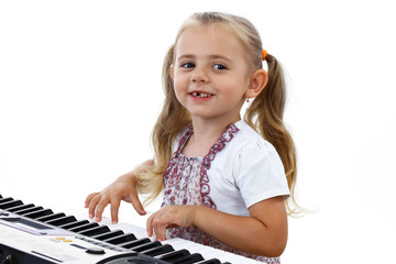 Little happy girl playing on a keyboard instrument.