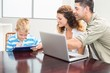 Happy parents showing son how to use tablet pc