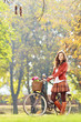 Smiling young female standing with bicycle in park and looking a