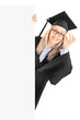 Young woman in graduation gown standing behind blank panel