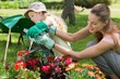 Mother and daughter watering plants at garden