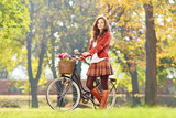 Smiling young female standing with bicycle in park