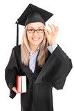 Young female student in graduation gown holding books