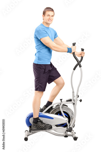 Young man working out on a cross trainer machine