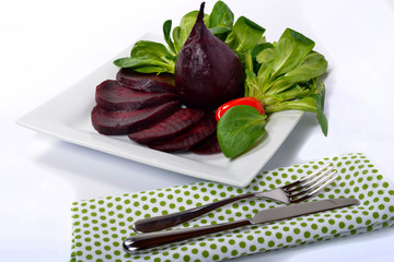 plate of beet salad with green towel, knife and fork