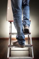 Man holding picture frame while climbing on ladder