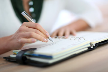 Closeup of woman's hand writing on agenda