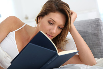 Woman reading book laid in bed
