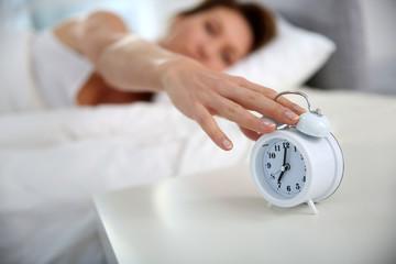 Woman turning alarm clock off in morning