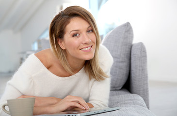 Beautiful blond woman at home websurfing on internet
