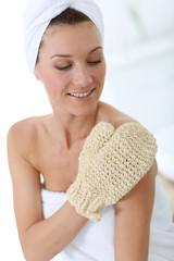 Portrait of beautiful woman using rubbing glove
