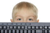 Little boy looks out keyboard
