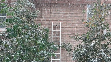 Snow Fall And Brick Wall With Ladder