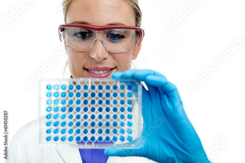 scientist woman examining a microplate