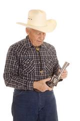Elderly man cowboy look at pistol