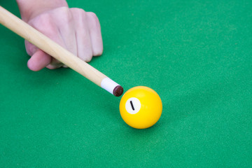 hand with billiard cue ready to hit the ball
