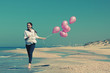 Young woman  walking on the beach with pink balloons. Photo in o