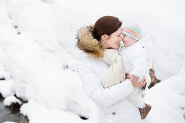 Happy young mother holding her baby in a snowy winter park