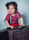 Little boy near old suitcase