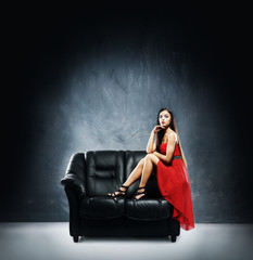 A beautiful woman in a red dress on a black leather sofa