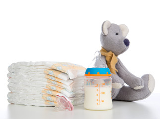 New born child stack of diapers, nipple soother, teddy bear toy