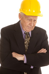 Elderly man suit hardhat arms folded look down