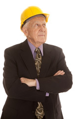 Elderly man suit hardhat arms folded
