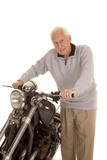 Elderly man holding motorcycle handlebars