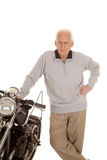 Elderly man stand by motorcycle