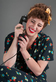 Pinup Girl in Flowered Outfit Laughs While on the Telephone