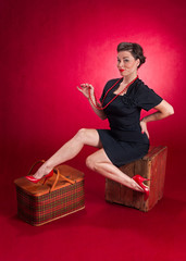 Pinup Girl in Black Dress Sits on Wooden Box