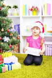 Little girl with letter for Santa near Christmas tree in room