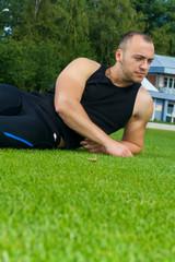 Image of muscle man sitting on stadium grass