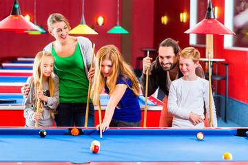 Familie spielt Poolbillard oder Billard