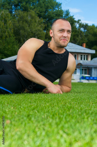 Image of muscle man sitting on stadium grass