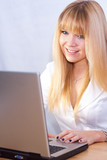 smiling girl chatting online with laptop