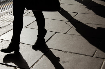 Silhouette of walking woman legs with boots