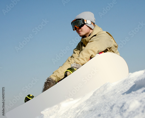 Snowboarder sitting on a ski slope