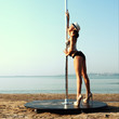Pole dance woman in hat against sea background.