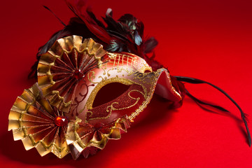 A red and gold feathered Venetian mask on red background