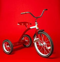 Vintage red tricycle on a bright red background