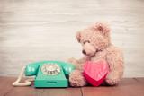 Fototapety Teddy Bear with heart box near retro telephone