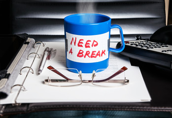 "Coffe mug with message ""Need a break"". Stress concept."