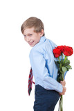 Cute funny little boy hiding a bouquet of red roses behind