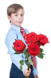 Beautiful romantic boy stretching a bouquet of red roses