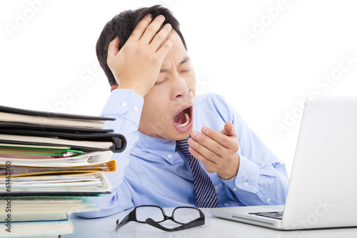 Exhausted young businessman yawning and holding his head