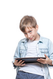 Cute stylish blond boy in a blue shirt holds tablet pc