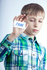 "Beautiful blond child shows a message ""Pain"" looking ill"